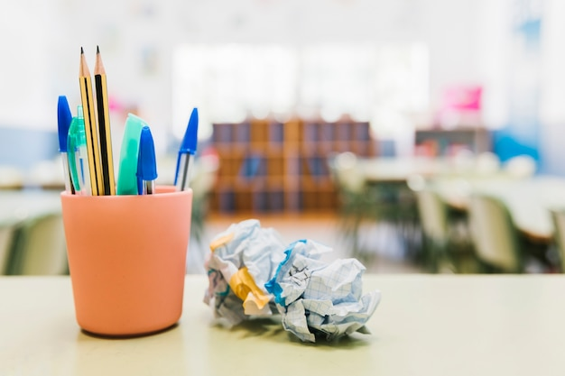 School stationery in cup on desk