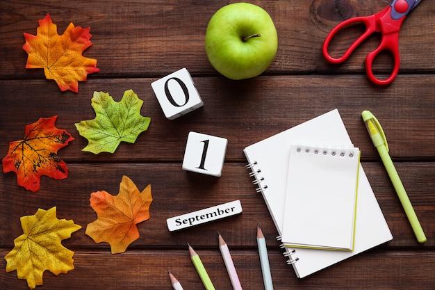 학교 문구류 녹색 사과 연필 가위는 학교 개념에 대한 탁자 위에 메모장을 열었습니다.