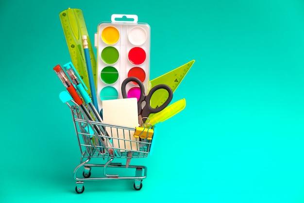 Обучите канцелярские принадлежности в магазинной тележкае игрушки на зеленой предпосылке. концепция подготовки к началу учебного года. копировать пространство