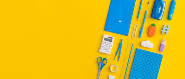 Школьные принадлежности на желтом фоне. вид сверху с копией пространства. плоская планировка. снова в школу концепции.