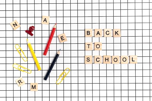 Школьные принадлежности на клетчатом белом фоне. снова в школу, концепция обучения. вид сверху, плоская планировка