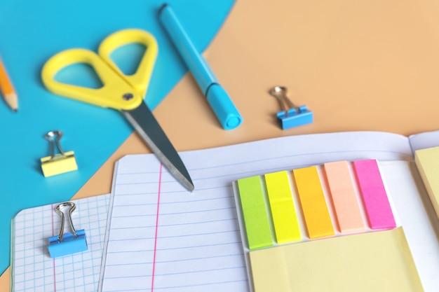 コピースペースとオレンジ色の青い背景に学校の文房具