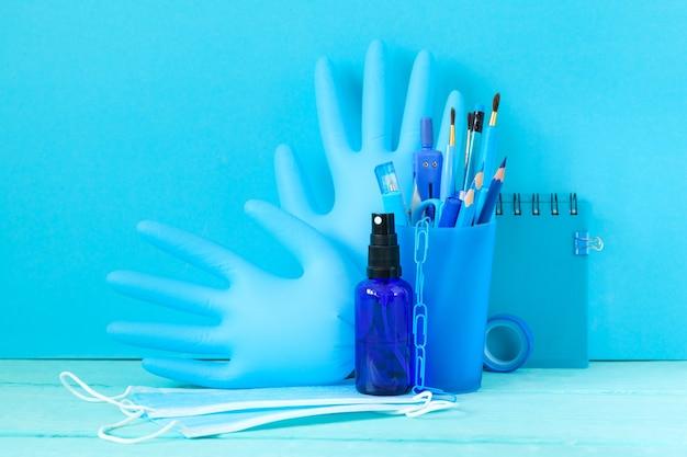 学校の文房具用品と医療用マスク、学校に戻るための手袋手の消毒剤