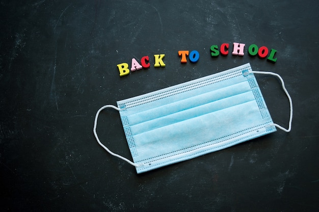 School stationery supplies, medical masks on the blackboard. back to school after covid-19 coronavirus.