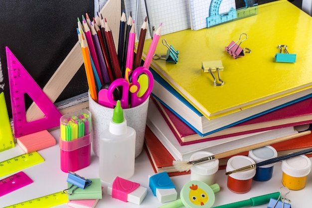 School stationery on a table in front of blackboard.
