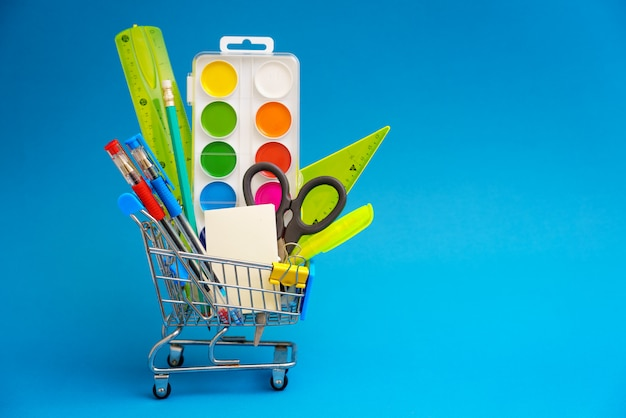 School stationery in  toy shopping cart on  blue background. the concept of preparing for the beginning of the school year. copy space