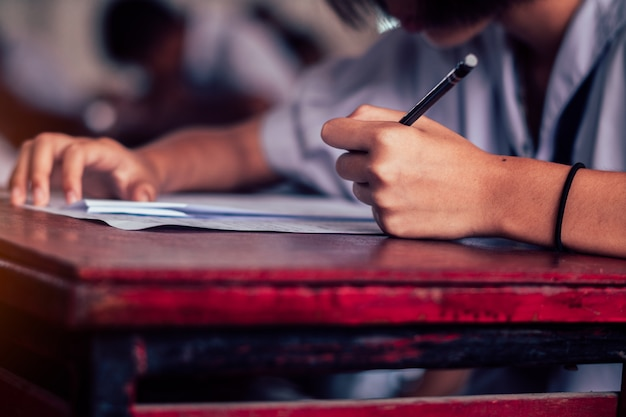 Студент школы принимает экзамен и писать ответ в классе для концепции теста образования.