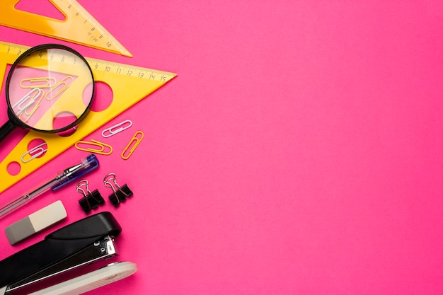School or student supplies on a pink background. back to school. magnifier, eraser, ruler, markers, paper clips, stapler