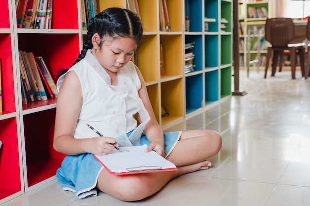 School student teenage girl drawing doing homework in library.education and literacy concept.