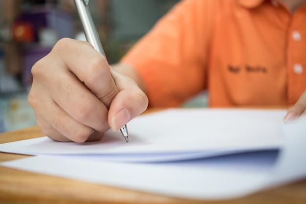 スクール学生は手を取って試験を受け、試験室には鉛筆をつかむ