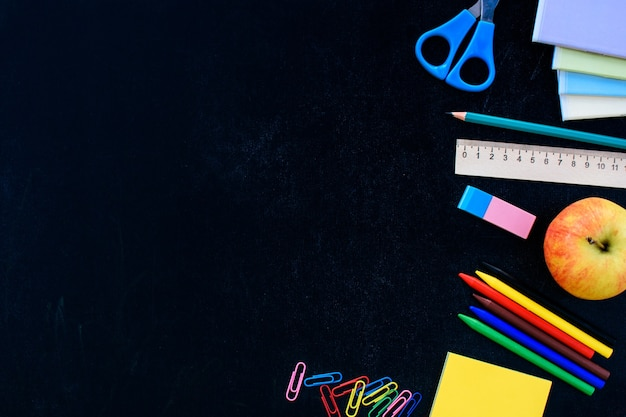 Школьные принадлежности на черной доске