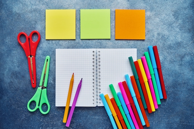 School subjects on a dark blue background. back to school concept. notepad, sticker pad, colored scissors and felt tip pens. flat lay, copy space