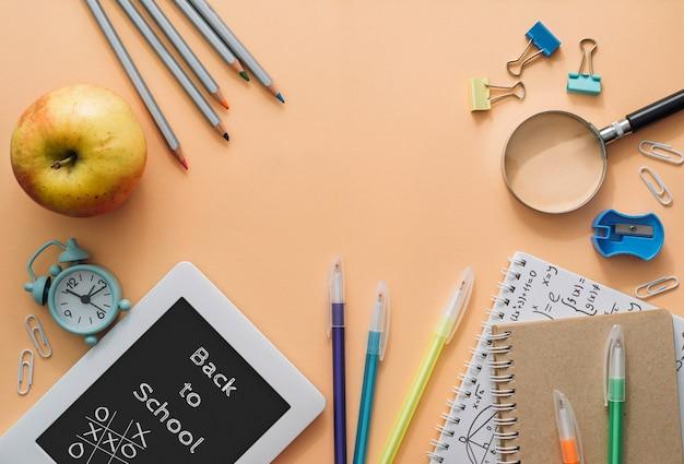 Школьные предметы в виде рамки на оранжевом фоне. снова в школу концепции. плоская планировка