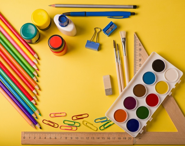 School supplies at abstract colorful background texture.