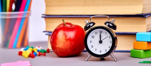 Школьные принадлежности и красное яблоко