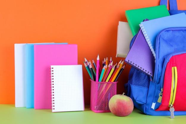Школьные принадлежности и школьный рюкзак на ярком разноцветном фоне