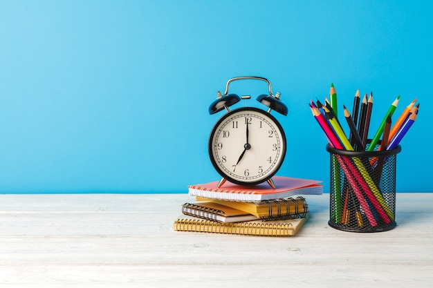 Школьные принадлежности и будильник на деревянном столе