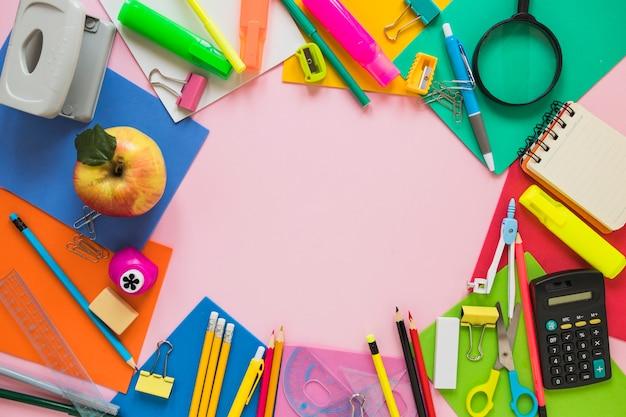 Школьные принадлежности и яблоко лежат в кругу