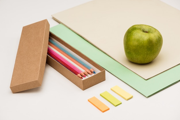 Школьные принадлежности и яблоко на белом столе