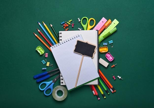 녹색 보드에 학용품과 검은색 테이블 램프. 다시 학교로 개념입니다. 디자인을 위해 조롱합니다. 공간을 복사합니다. 교육 개념입니다.