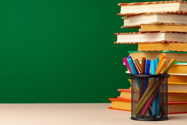 Школьные принадлежности и книги на столе на зеленой доске