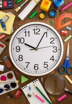 Школьные принадлежности и часы на деревянном столе
