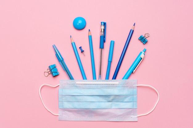 Школьные принадлежности и средства профилактики covid возвращаются в школу во время концепции пандемии на розовом бак ...