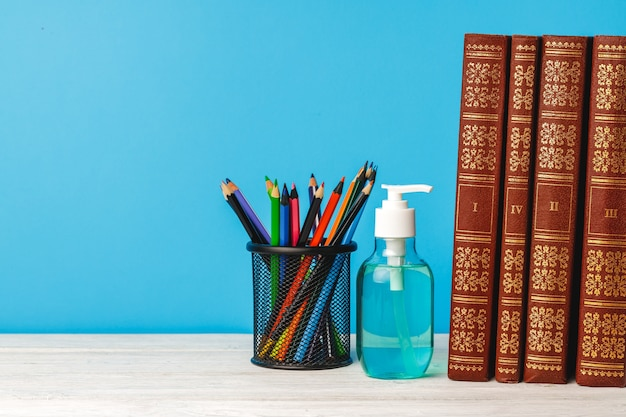 Школьные принадлежности и дезинфицирующее средство для рук на столе