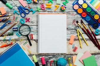 School supplies and notebook on wood background.