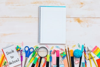 School supplies and notebook on wood background
