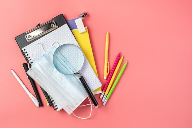 ピンクの背景に学用品と保護マスク。上面図。学校に戻る。