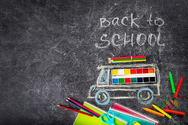 학교 용품 및 칠판에 분필로 그린 스쿨 버스