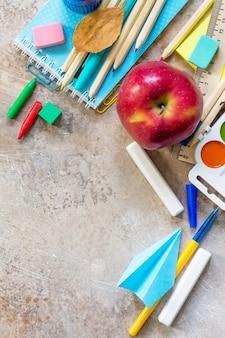 Школьные принадлежности яблоко и самолет оригами на светлом каменном или шиферном фоне копирование пространства
