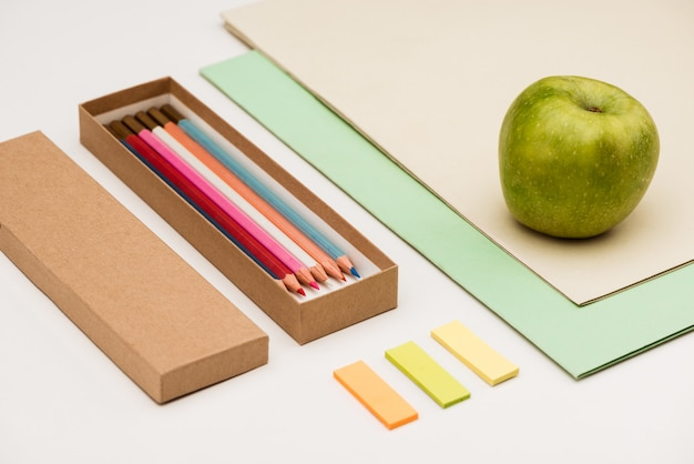 School supplies and apple on white table