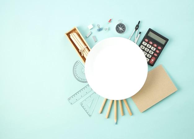 空の白い皿の周りの学用品
