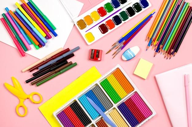 School supplies arrangement on a pink background