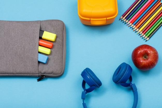 Школьные принадлежности. сумка-пенал с цветными фломастерами и маркером, ланч-бокс, цветные карандаши, яблоко и наушники на синем фоне. вид сверху. вернуться к школьной концепции