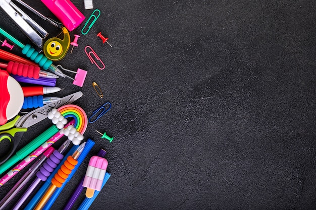 School supplies on black board background with copy space, back to school