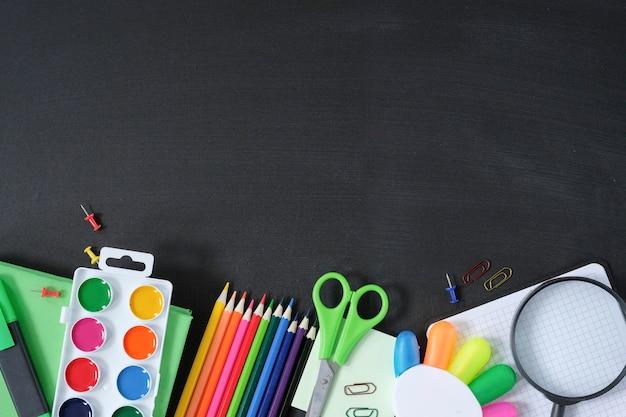 School supplies on black board background.