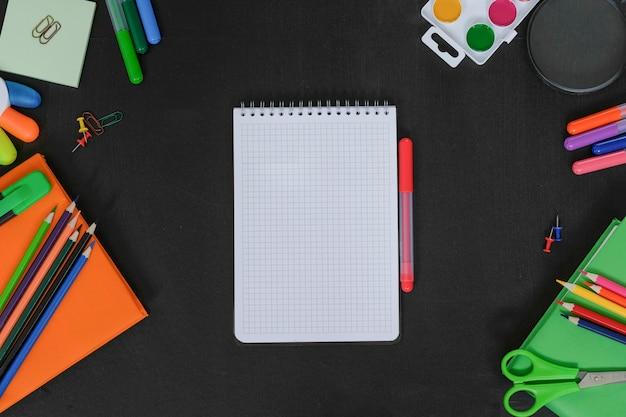 School supplies on black board background