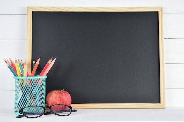 School supplies on black board and white wood