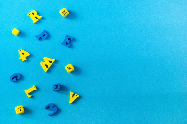 School supplies on a blue background. school and teacher day concept. wooden letters on the table with copy space .