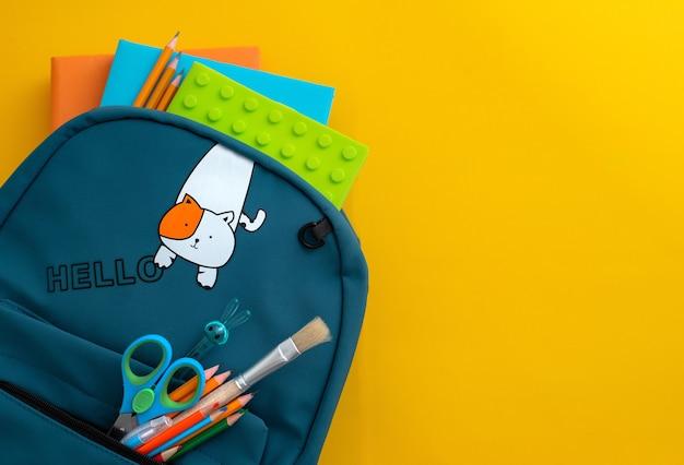 Школьные принадлежности синий рюкзак медицинская маска желтый фон обратно в школу кон ...