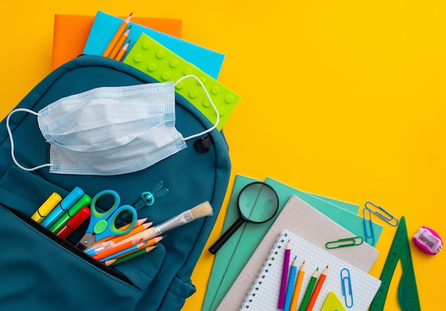 School supplies, blue backpack medical mask on yellow