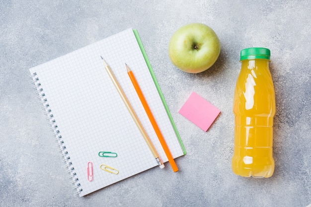 School supplies and breakfast crackers, orange juice and fresh apple