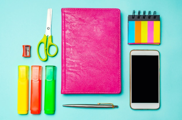School supplies on a bright blue background, top view, concept of education, desktop, creative