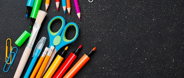 School supplies on the chalkboard, top view. free space.