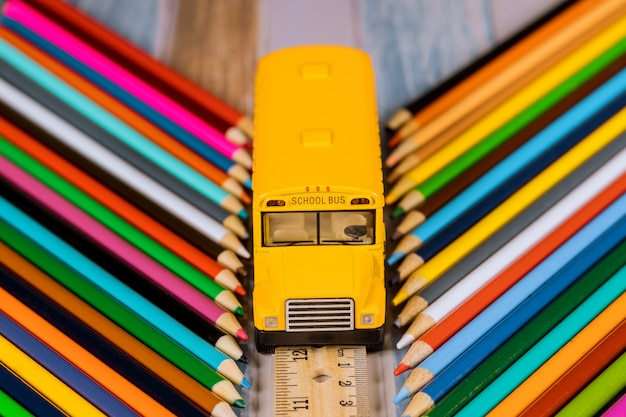 School supplies, colored pencils and toy student bus. education concept.