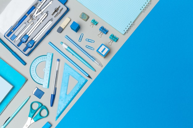 School supplies at colorful paper background with copyspace
