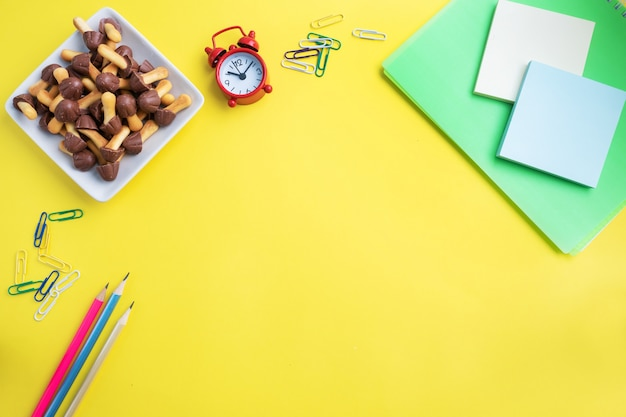 School supplies and cookies for a snack on the yellow table with copy space. concept school